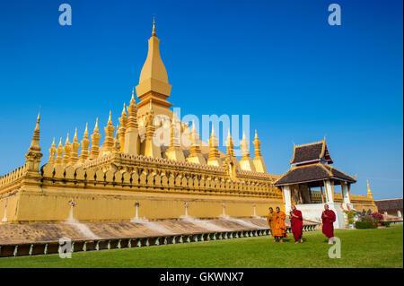Vientiane, Laos - January 19, 2012:  Group of Buddhist monks walking around That Luang Stupa, landmark of Vientiane, - Stock Photo