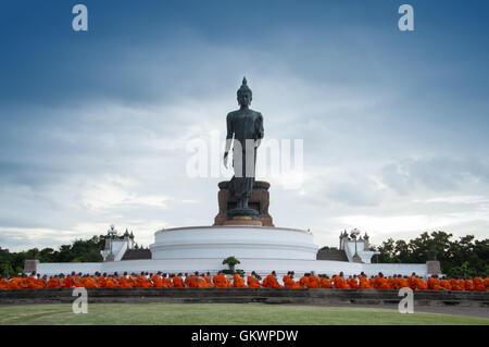Nakhon Pathom, Thailand - August 4, 2016: Buddhist monks praying in front of walking Buddha statue at Buddhamonthon - Stock Photo