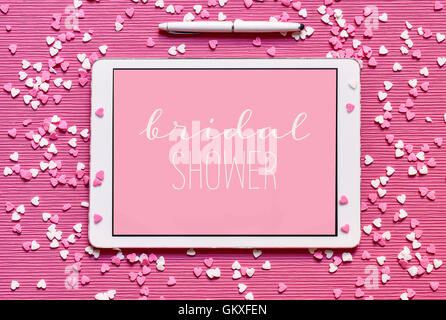 high-angle shot of a tablet with the text bridal shower written in white in it against a pink background, placed - Stock Photo