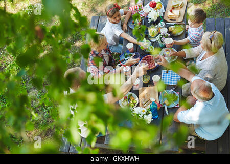 Family members gathered by dinner table outdoors - Stock Photo