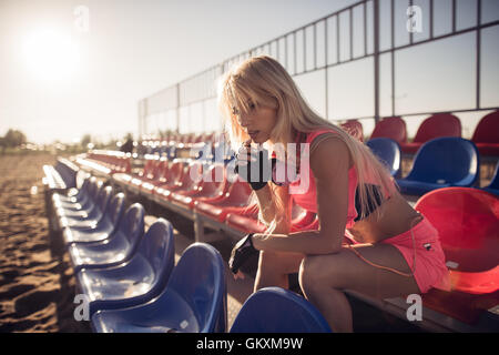 Attractive female runner seated on the beach resting after intensive volleyball game, female runner on the summer - Stock Photo