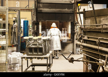 workmen in safety wear cutting, grinding metal parts for further processing manufacturing component parts for assembly - Stock Photo