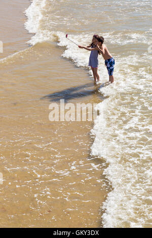 Bournemouth, Dorset, UK 23 August 2016. Young couple taking a selfie on a hot sunny day at Bournemouth beach. Credit: - Stock Photo