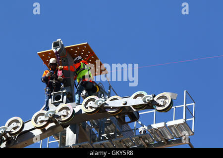 El Alto, Bolivia, 23rd August 2016. Technicians install a light synthetic cable on the pylon of a new cable car - Stock Photo