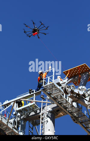 El Alto, Bolivia, 23rd August 2016. A technician reaches for a light synthetic cable that is being carried by a - Stock Photo
