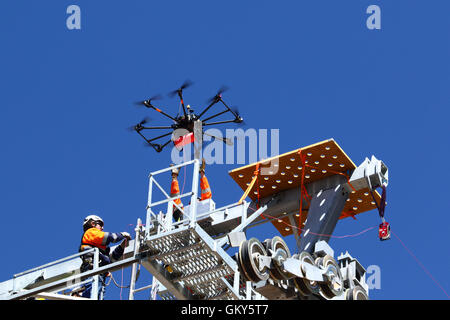 El Alto, Bolivia, 23rd August 2016. A technician reaches for a drone that is carrying a light synthetic cable between - Stock Photo