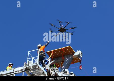 El Alto, Bolivia, 23rd August 2016. A technician reaches for a drone as it lands on top of a cable car pylon. The - Stock Photo