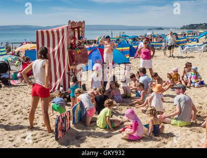 Children watching a Punch and Judy Show on Bournemouth beach, Dorset, UK - Stock Photo