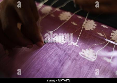 Near Dhaka, Bangladesh. 24th Aug, 2016. Handloom weaver weaves Jamdani saree on a traditional wooden hand weaving - Stock Photo