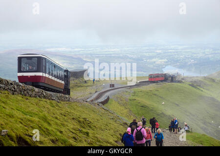 Train descending on Snowdon Mountain Railway above Clogwyn Station and people walking on Llanberis path on Mt Snowdon - Stock Photo