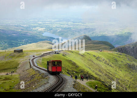 Train climbing up on Mt Snowdon Mountain Railway line above Clogwyn Station and people walking on Llanberis path - Stock Photo