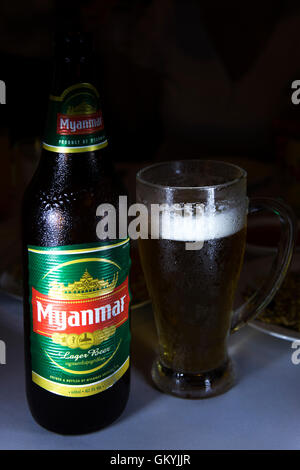 A cold bottle of Myanmar beer is served at a restaurant in Bagan, Myanmar (Burma). The beer has been poured into - Stock Photo
