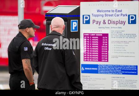 Black uniformed Civil Enforcement officers in Topping Street, Blackpool, Lancashire, UK - Stock Photo