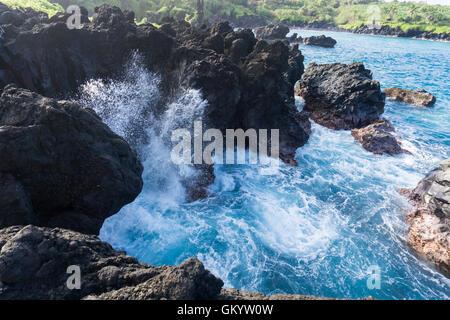 Ocean wave breaking against rocks in Hawaii - Stock Photo