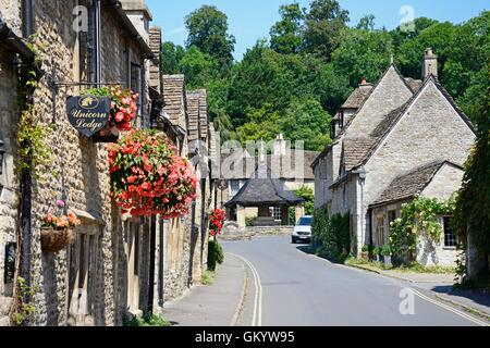 View along the main village street towards the fourteenth century market cross in the village centre, Castle Combe, - Stock Photo