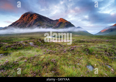 Stunning sunrise over a cottage beneath the mountains at Glencoe in the Scottish Highlands