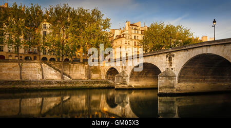 Morning sunlight on Ile Saint Louis and aspen trees lining the Seine river bank by Pont Marie and Quai d'Anjou. - Stock Photo