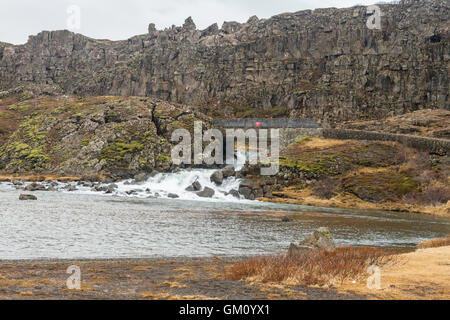 Bridge and waterfall with rock wall behind, Þingvellir National Park, Iceland, former site of the Icelandic Parliament. - Stock Photo