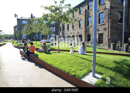 People relaxing on the grass on Wharf Road, near Granary Square, in the Kings Cross regeneration area, in London - Stock Photo