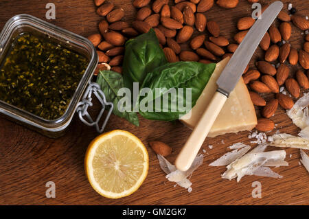 Homemade pesto ingredients basil fresh almonds lemon salt dressing flavor parmesan leaves ground italian - Stock Photo