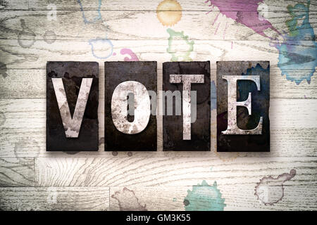 The word 'VOTE' written in vintage dirty metal letterpress type on a whitewashed wooden background with ink and - Stock Photo