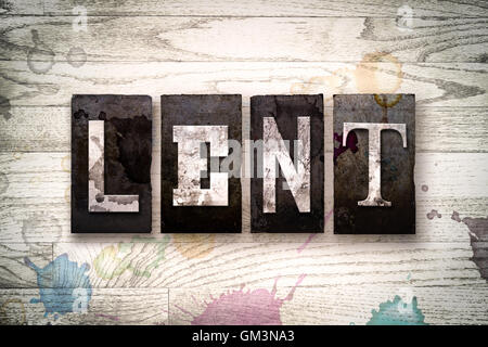 The word 'LENT' written in vintage dirty metal letterpress type on a whitewashed wooden background with ink and - Stock Photo