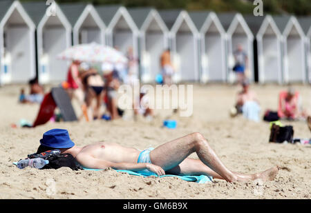 A man sunbathes on Branksome Chine Beach in Bournemouth, as a heatwave causes parts of the country to sizzle. - Stock Photo