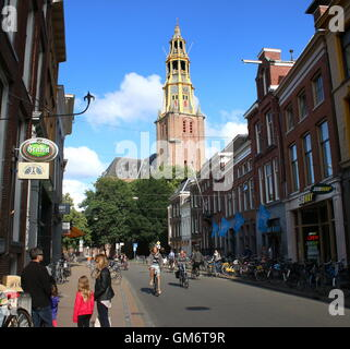 People shopping in Brugstraat (Bridge Street) in Groningen, Netherlands. 17th century church Der Aa-Kerk in background. - Stock Photo