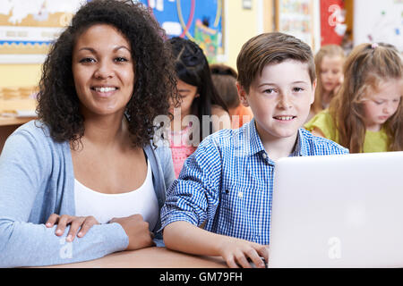 Teacher Helping Male Elementary Pupil In Computer Class - Stock Photo