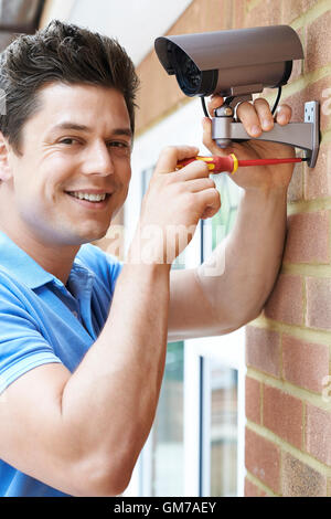 Security Consultant Fitting Camera To House Wall - Stock Photo