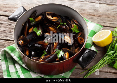 Mussels in copper on wooden table - Stock Photo