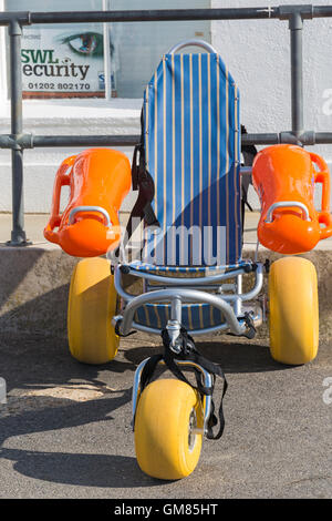 Floating beach wheelchair available for disabled less-abled to use on the beach at Poole, Dorset - Stock Photo