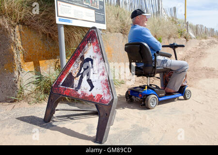 Disabled man on mobility scooter, on Mariners Way, Crosby, Liverpool, Merseyside, UK - Stock Photo