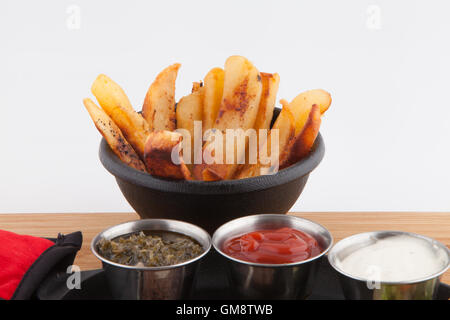 French Fries  garnish sauces Ketchup catsup table sauce Ranch dressing, Chimichurri on a cast iron - Stock Photo