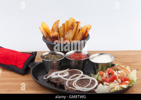 Flank steak,French Fries fresh garnish sauces Ketchup catsup table sauce Ranch dressing, Chimichurri cast iron skillet - Stock Photo