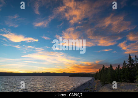 Dramatic colorful sunset seen from the shore of Yellowstone Lake in Yellowstone National Park - Stock Photo