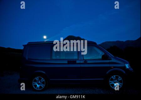 van & rising moon in English lake district - Stock Photo