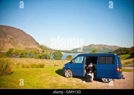 man & dog in van next to Crummock water in cumbria lake district, england - Stock Photo