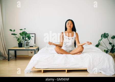 Young woman practicing yoga on bed - Stock Photo