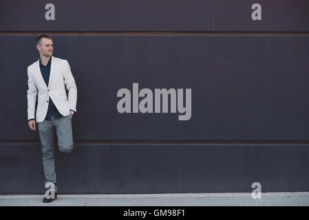 Businessman standing in front of dark wall - Stock Photo
