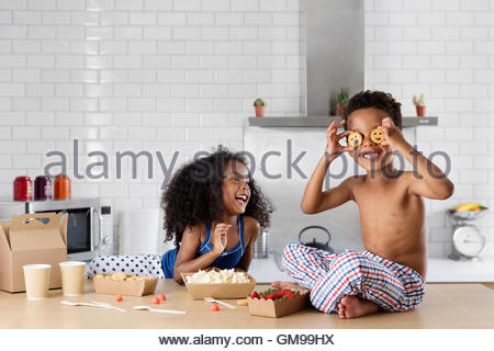 Little boy covering his eyes with cookies while sister watching him - Stock Photo