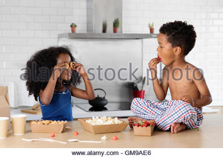 Little girl covering her eyes with cookies while brother watching her - Stock Photo