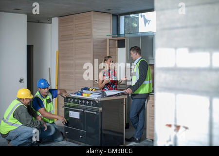 Architect and woman discussing kitchen furnishing - Stock Photo