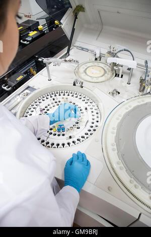 Laboratory technician in analytical laboratory using autoanalyzer - Stock Photo