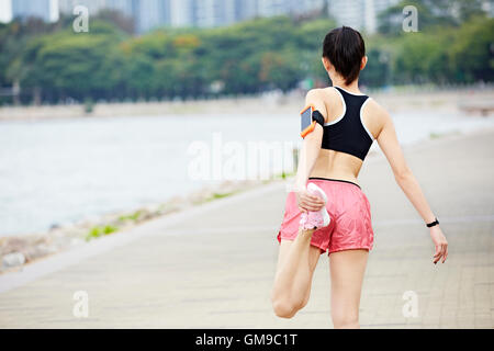 young asian female runner warming up by stretching leg before running in a city park. - Stock Photo