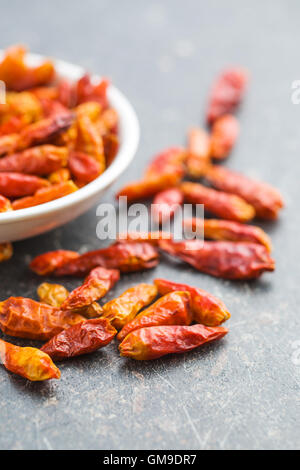 Dried mini chili peppers on kitchen table. - Stock Photo