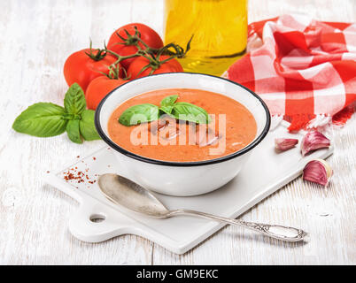 Cold gazpacho soup with ice, basil and fresh tomatoes - Stock Photo