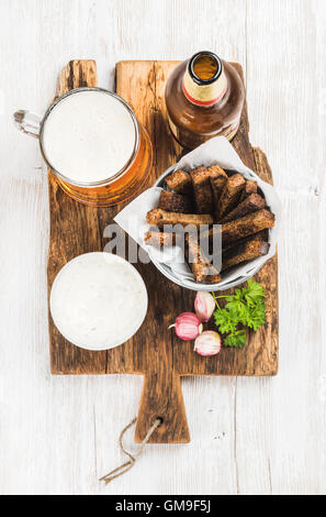Beer snack set. Pint of pilsener in mug, open glass  bottle, rye bread croutons with garlic cream cheese sauce on - Stock Photo
