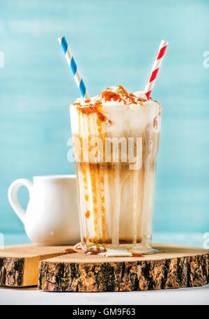 Latte macchiato with whipped cream and caramel sauce in tall glass on wooden board over blue painted wall background - Stock Photo