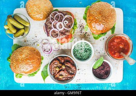 Homemade beef burgers served with pickles, spices, tomato sauce - Stock Photo